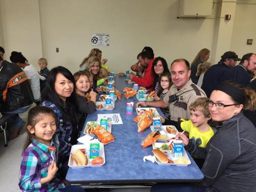 Parents sit with their children during Take Your Parent To Lunch Day at Jackson County Central Schools (MN)